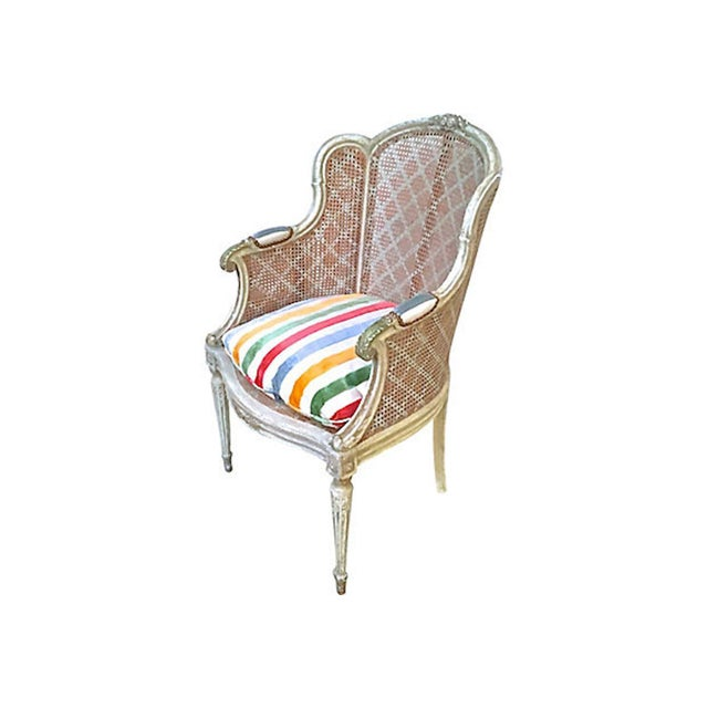 Antique French hand-carved rattan wingback chair with multicolored striped velvet upholstered arm pads and seat cushion....