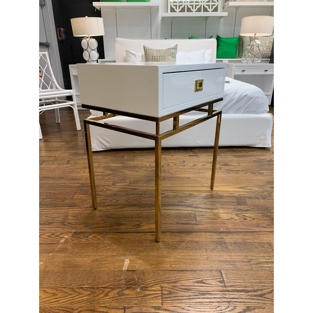 White lacquer and brass side table. With one drawer, a brass base, and campaign hardware, this side table is the perfect...