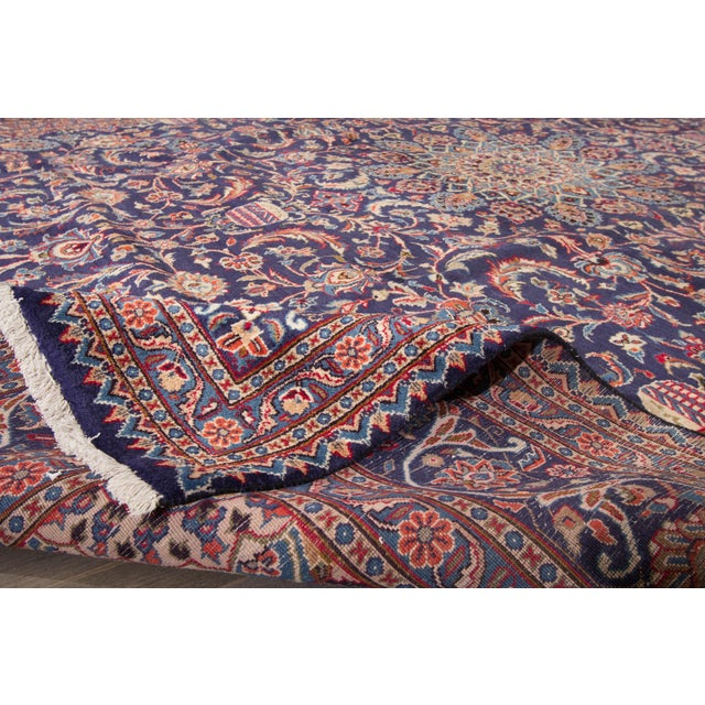 A hand-knotted Kashan rug with a floral medallion design on a blue and red field. This amazing vintage rug is perfect for...