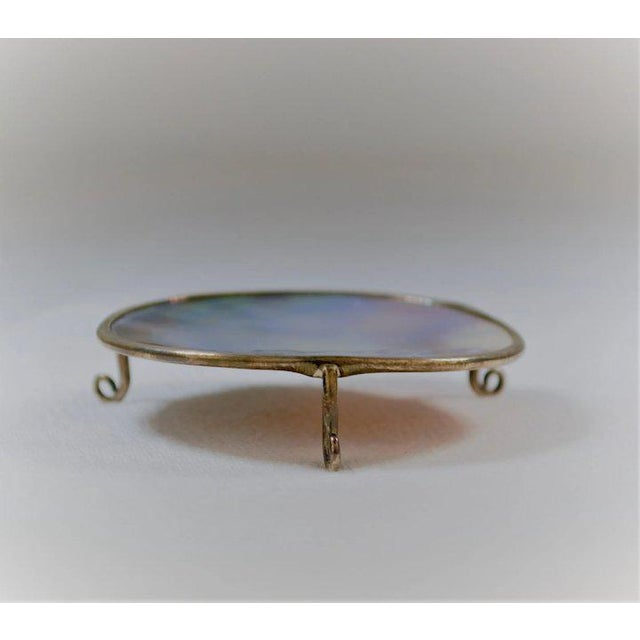 A fascinating miniature platform made of mother of pearl shell encased in a sterling band with three feet. If you are a...