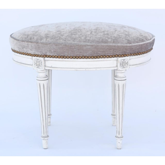 Oval stool, having a boxed seat in mushroom chenille with nailheads, on white painted frame showing natural wear, on...