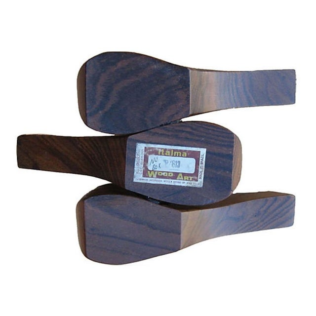 "A pipe rack which looks like 3 pipes sculpted in rosewood. It wear the label ""Jean Gillon, Italma Wood Art."""