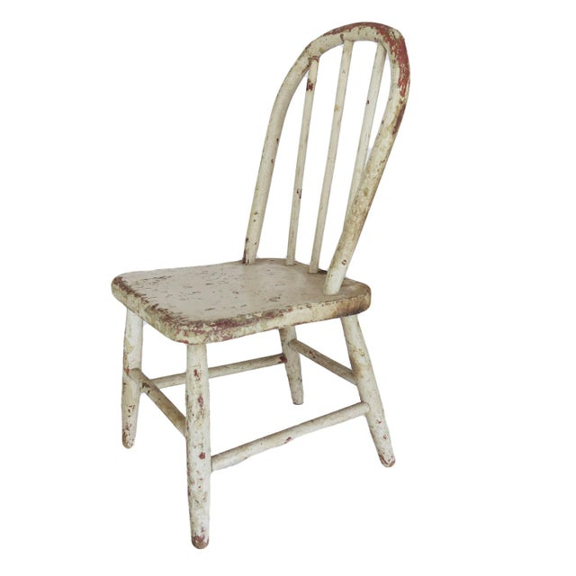 """Vintage child-sized white wooden chair. Measures 21"""" tall x 11"""" wide x 10"""" deep; seat height is 9 1/2""""."""