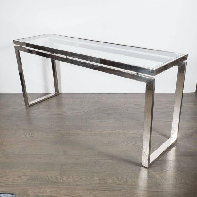 This very sleek Mid-Century Modernist chrome and glass console or sofa table features a sleek and stylized chrome base...