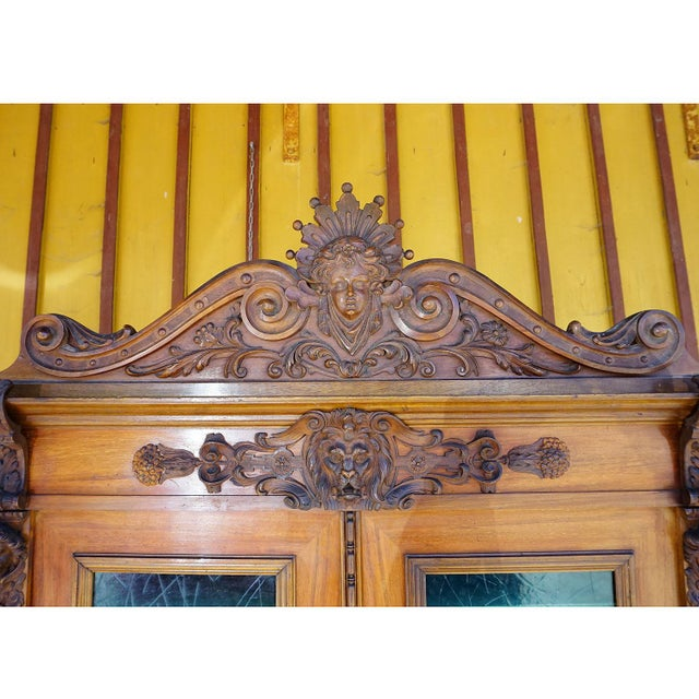 a detailed handcarved wooden buffet or cupboard with several elaborately carved wooden decorations depicting lion,...