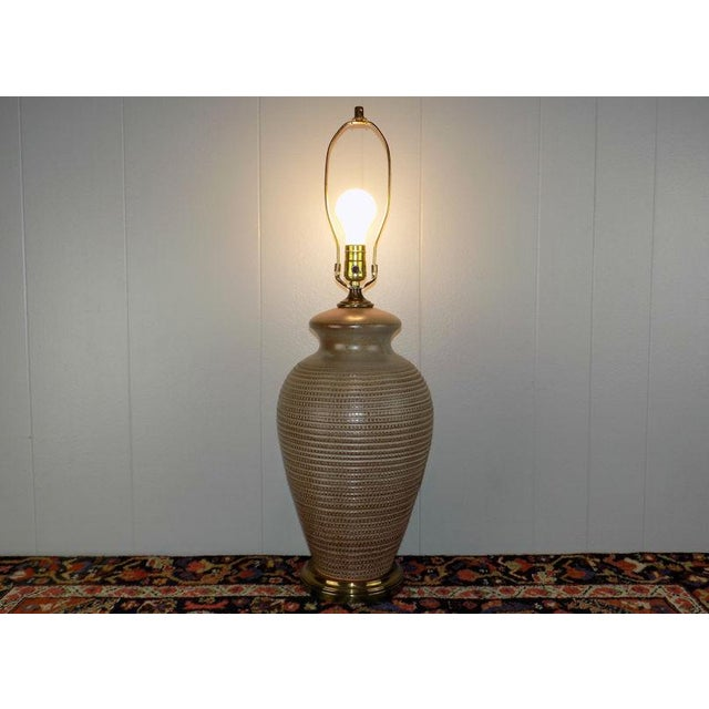 Big scale pottery lamp with an intense, hand incised pattern and a brown slip glaze, made in Italy.This is marked on the...