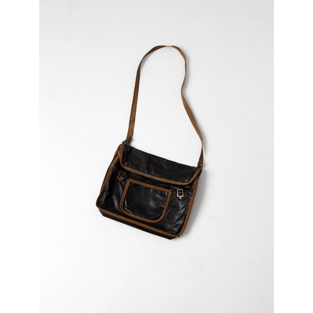 This is an original vintage American school bag circa 1910-1920. The painted black canvas bag features natural toned trim....