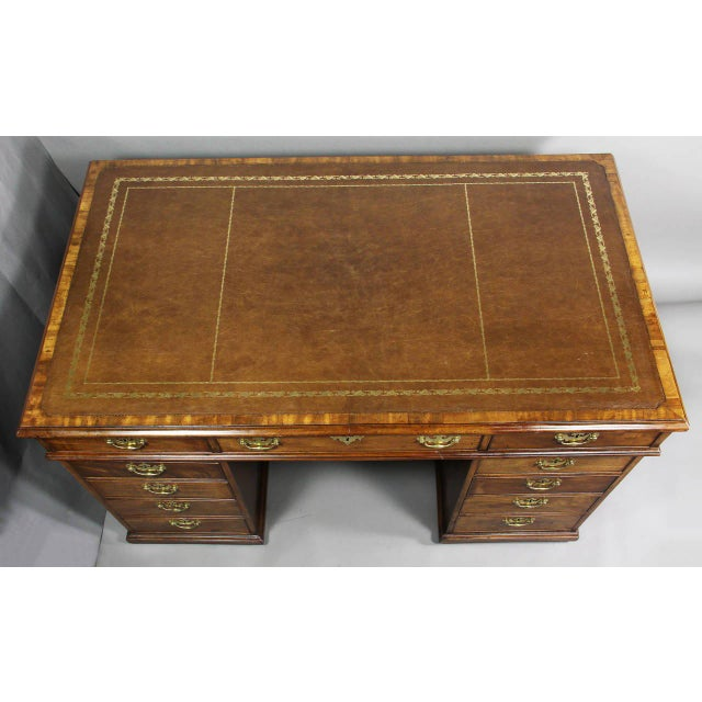 Desk with brown tooled leather top with crossbanded edge over one long flanked by a pair of short drawers, pedestal base...