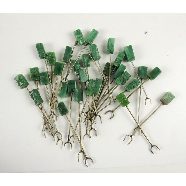 Set of 32 green onyx and silver carved hors d'oeuvre picks. 2 sets of 16 each of slightly different sizes. Some wear,...