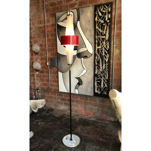 Futuristic oval shaped frosted glass fits at the top of a black enameled pole, the oval glass is surrounded by an orange...