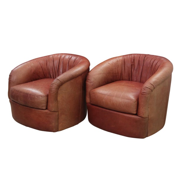 A pair of vintage leather swivel club chairs. Rounded backs and arms are upholstered throughout in a rich brown leather...