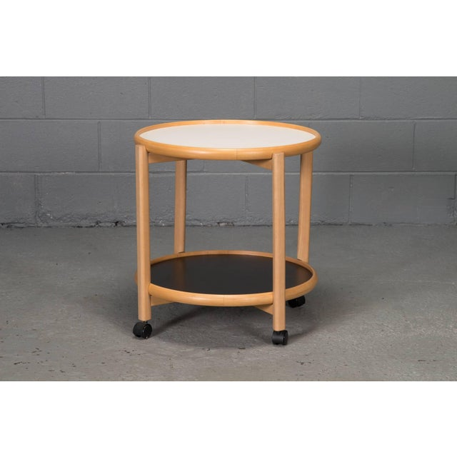 Two-tier reversible top beech and laminate side table on casters. Top is removable and reverses from black to white.