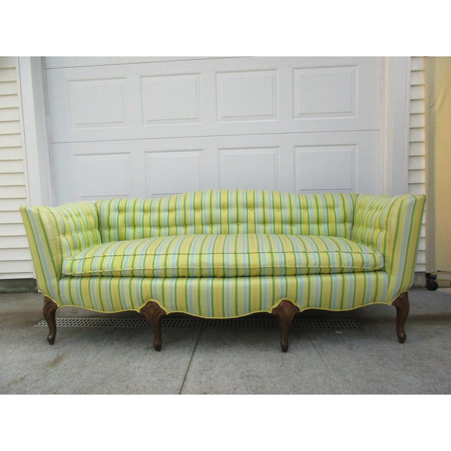 This vibrant French style sofa sits atop seven short cabriole legs; four in the front and three in the back. It is tufted...