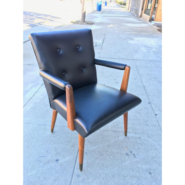 A very unique and usual arm mid-century American arm chair. Solid Walnut construction with original black vinyl...