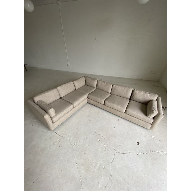Sleek and simple, newly upholstered mid century sectional in a woven textured tan fabric. In excellent condition....