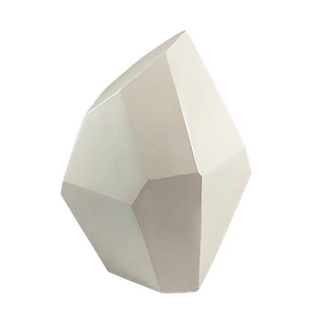 This white crystal-shaped sculpture, made of resin, adds an element of drama and sophistication to any space.