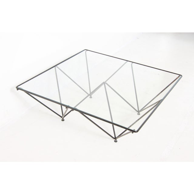 Beautiful clean and modern glass and lacquered iron coffee table in the style of Paolo Piva. Feet at bottom are adjustable...