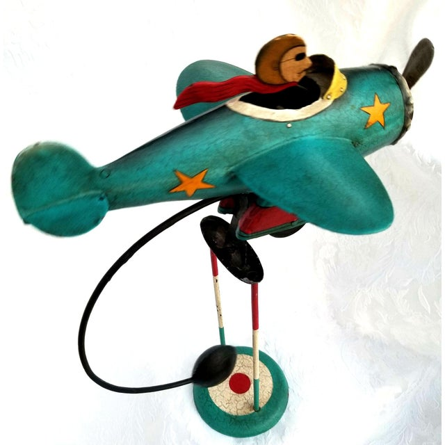 An unusual, hand painted, vintage aviator and his airplane are crafted of metal. The piece is a fascinating example of...