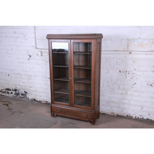 A beautiful antique carved oak glass front bookcase or display cabinet. The bookcase features solid oak construction, with...