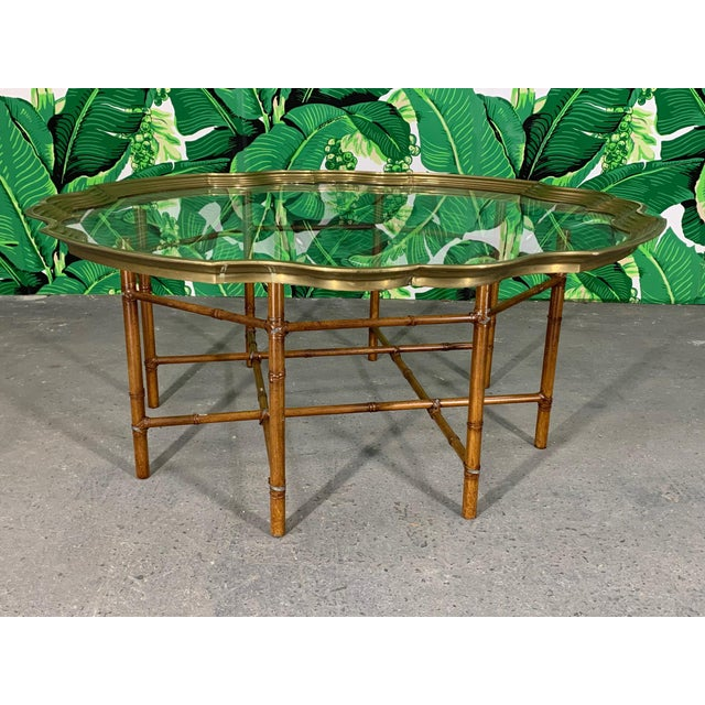 Vintage faux bamboo coffee/cocktail table features metal frame and glass tray top rimmed in solid brass. Good vintage...