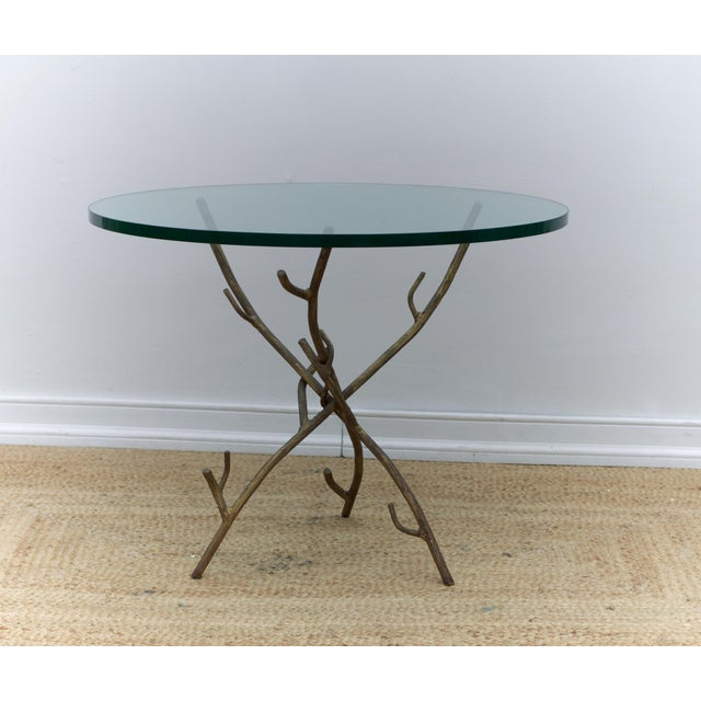 A unique and funky faux bois iron tripod based cocktail table of branch form having a chunky glass top, (we can sell and...