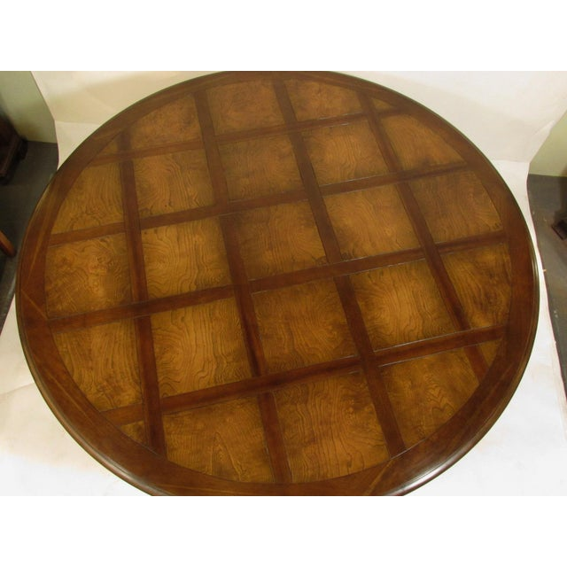 A fine quality Louis XVI style black cherry and ash pedestal base center table with parquetry top and walnut stain hand-...