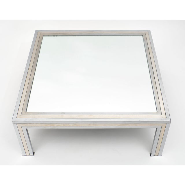 Chrome and mirror vintage French coffee table. This modernist piece has a solid chrome and brass structure with a mirrored...