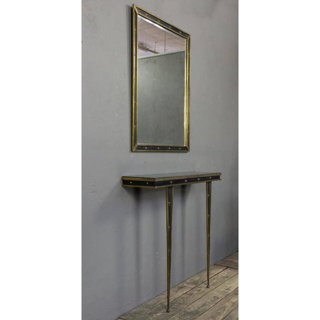 "Italian 1950s brass and iron console (36"" H x 39.5"" W x 11"" D) with black glass top and matching wall mirror (39.5"" H x..."