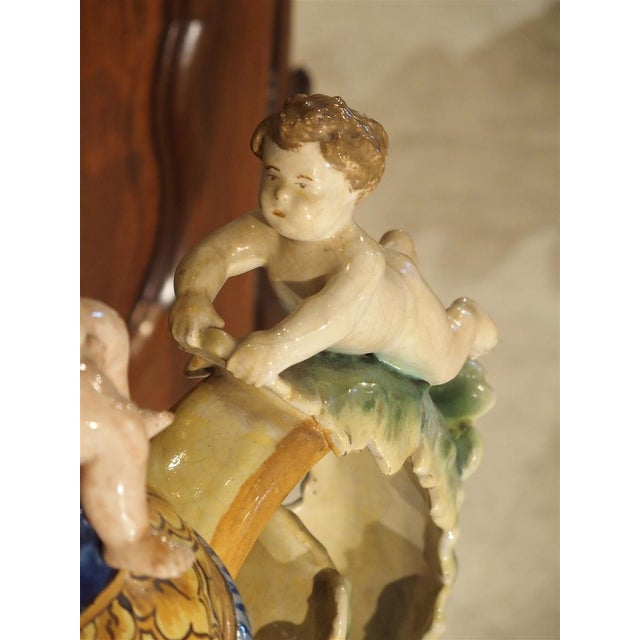 From Italy, this large, hand painted Majolica urn dates to the late 1800's. At the top are two putti seated upon the lid...