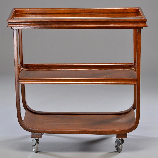Bar or tea trolley made of dark stained wood with removable, glass-covered top tray. Found in England, circa 1940s....