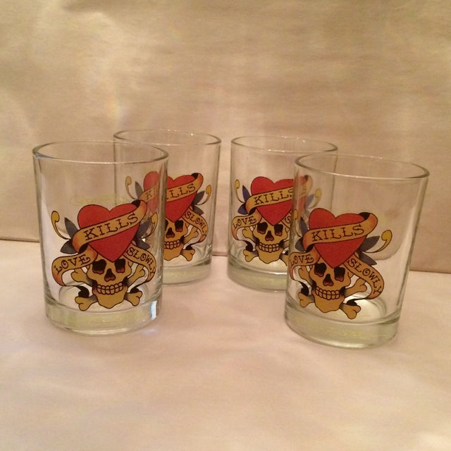"""Set of 4 """"Love Kills Slowly"""" weighted bottom low ball glasses by Ed Hardy. Great contemporary pieces to add to your home bar."""