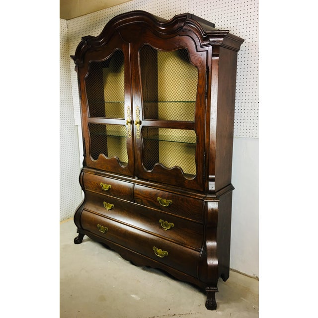This is A Bombay style china cabinet in dark oak. The cabinet has solid brass hardware. This cabinet features hand carved...