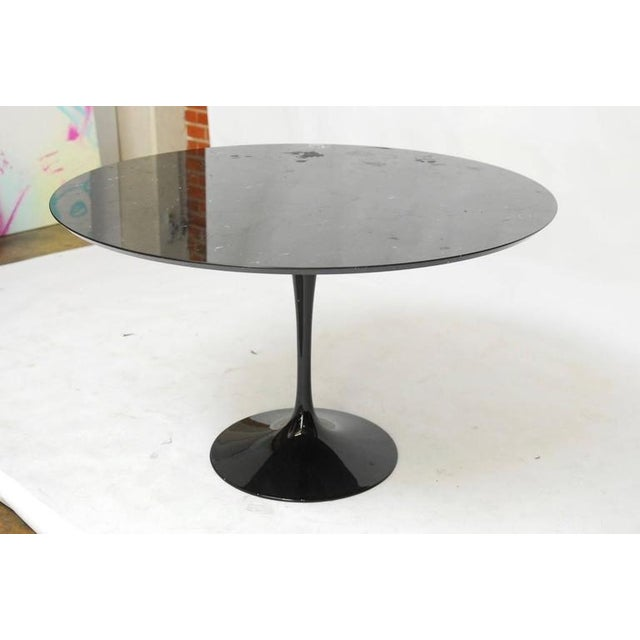 Dramatic Mid-Century Modern tulip dining table featuring a large round black marble top with white veining. Supported by a...