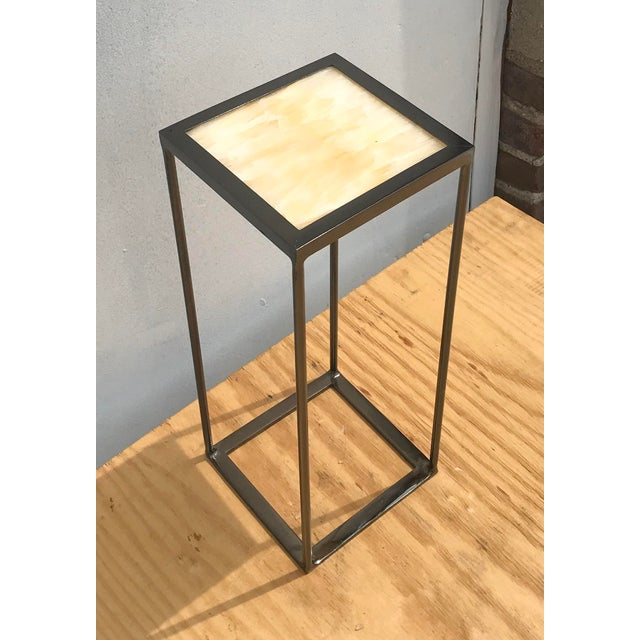 Sleek side table featuring an onyx square top insert and metal base. After being welded it then gets electroplated to...