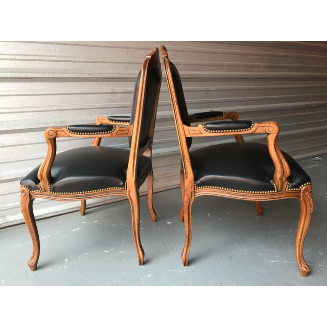 Pair of vintage Italian carved walnut French country or Louis XV style armchairs by Chateau d'Ax spa. Chairs feature black...