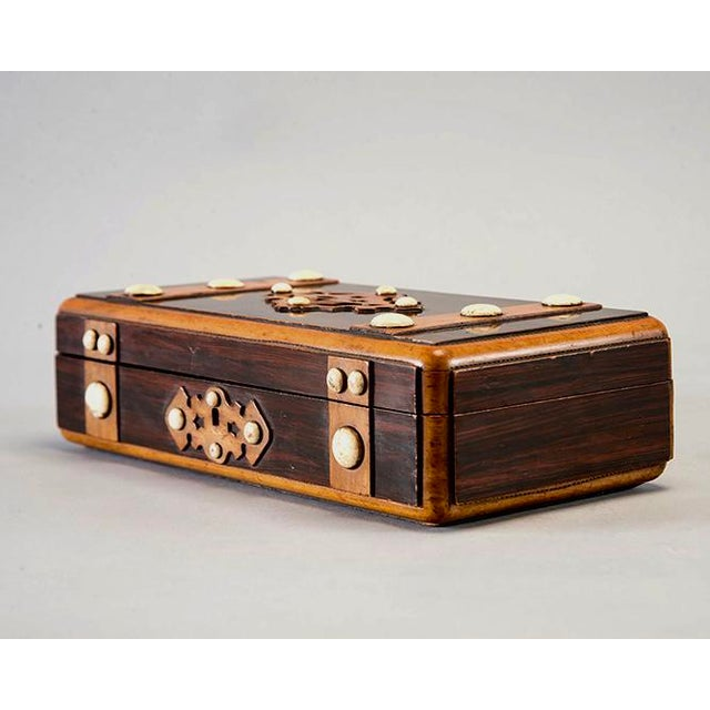 Early 20th century French game box is made of mahogany with inlay details and white stone embellishments, circa 1920s....