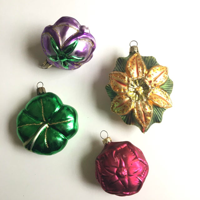 Set of four blown glass chistmas ornaments in the shape of flowers and shamrock - possibly Irish fowers. Decorated...