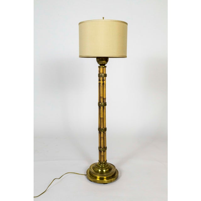 A modern, mid 20th-century floor lamp of bamboo stalks artfully bound with brass wire and capped with a brass ball under...