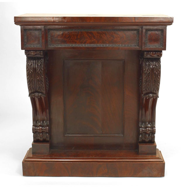 English Regency mahogany console table with carved scroll design sides framing a solid back panel with a platform base and...