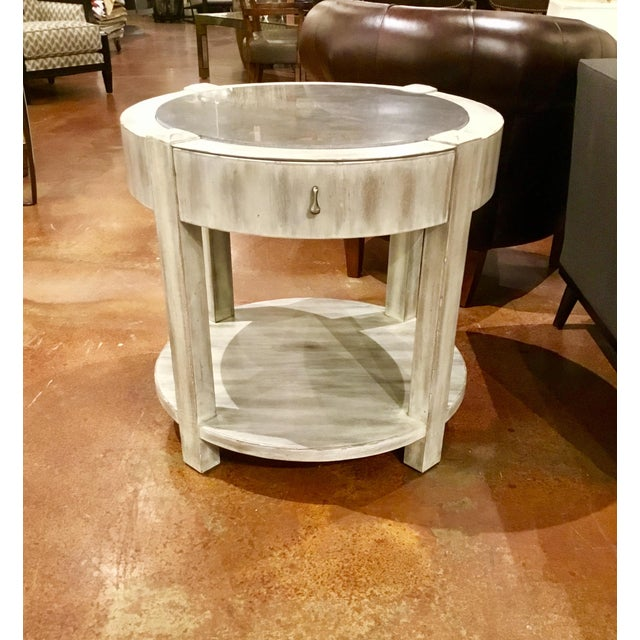Original Retail $1498, Transitional round end table by Drexel Heritage, with an off-white antique wood finish and black...