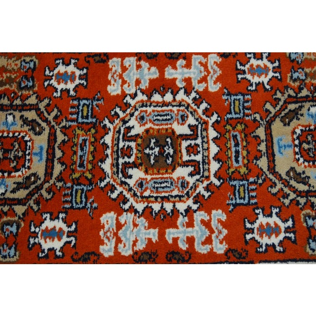 Vibrant tribal-style, hand knotted wool carpet featuring multi-colored field over a rust ground. Thick high wool pile...