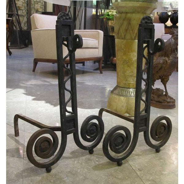 A dramatic and large-scaled pair of French art deco hand-wrought iron andirons; each of open rectilinear form with inset...