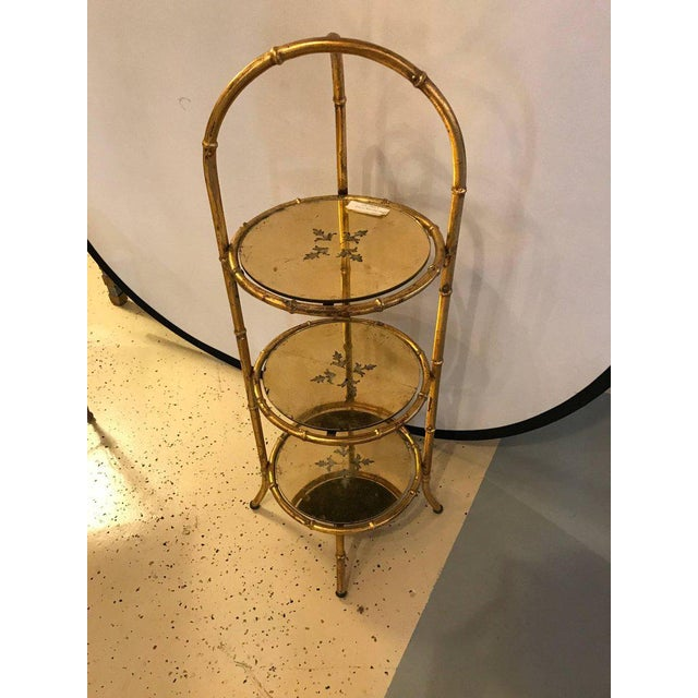 Faux bamboo églomisé three-tier etagere Stand. Nice and finely decorative three-tier Stand of gilt metal design having...