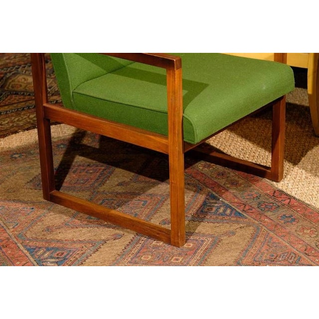 This original mid-20th century armchair features a clean-lined frame in rich teak wood with original green upholstery. Its...
