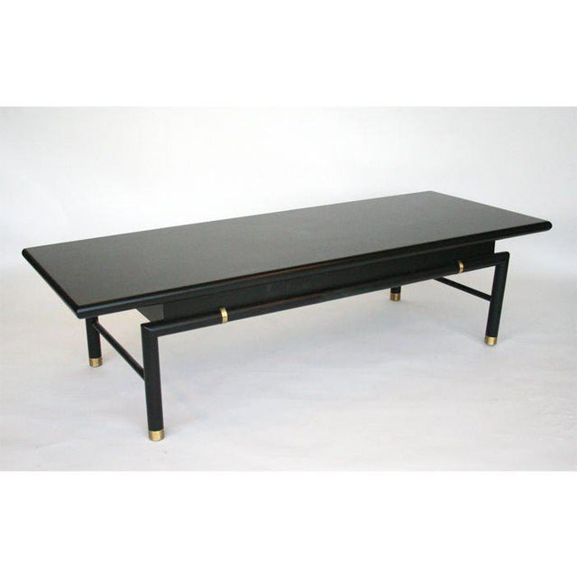 Ebonized coffee table with brass sabot and accents to frame. Cylindrical legs turn to create a base for the floating top....