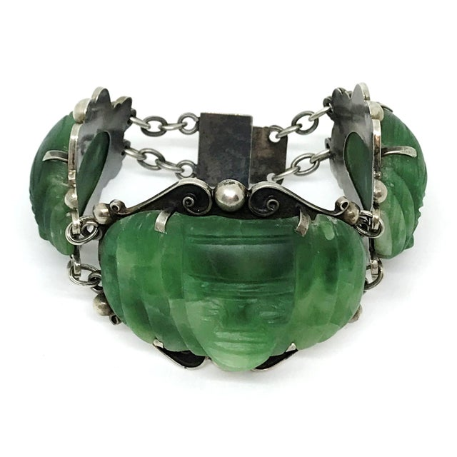 Circa 1930s to 1940s artisan made, sterling silver large link bracelet. It is prong set with hand carved, green onyx masks...