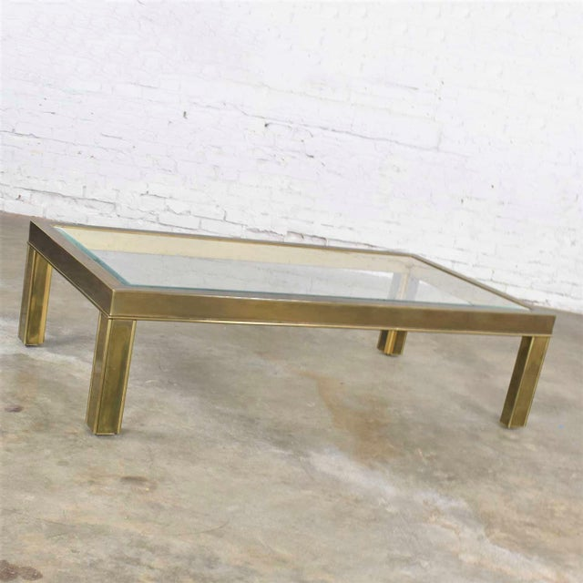 Handsome large modern brass and glass parsons' style coffee table or cocktail table in the style of Mastercraft. It is in...