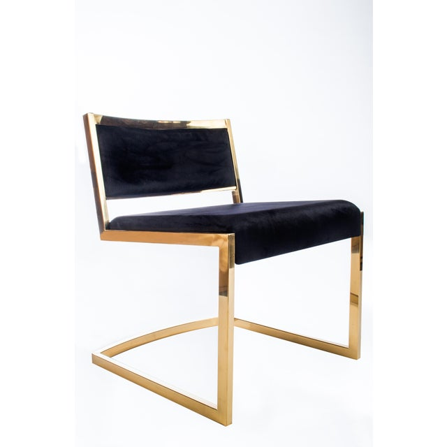 This is a new chair, never been used. This modern chair features a stainless steel frame and a black velvet upholstery...