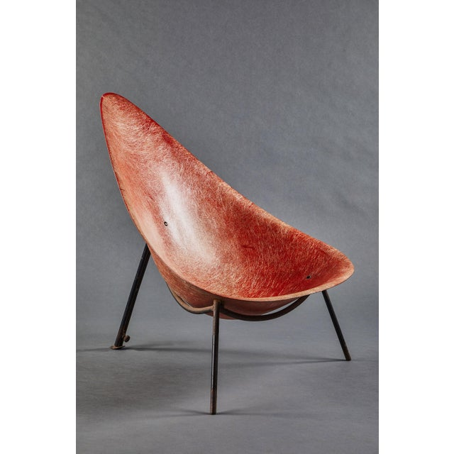 An early French Merat fiberglass easy chair in red colored fiberglass with black painted steel legs.