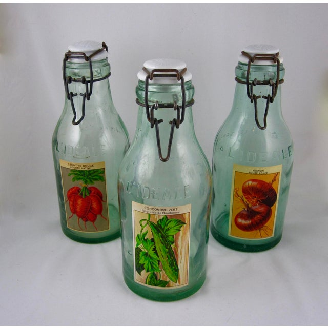 A set of three, large French green glass canning preserve jars, circa early 1900's. The traditional porcelain lids are...
